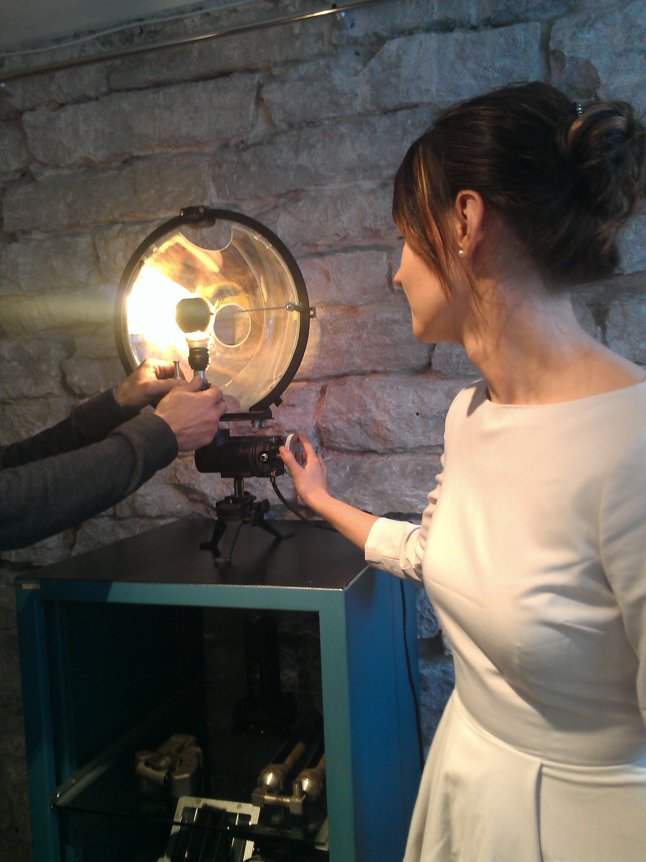 Ain's daughter Leili demonstrates how this lamp, made from an old vehicle headlamp, can be adjusted to expose more or less light, or to change the angle at which it shines.