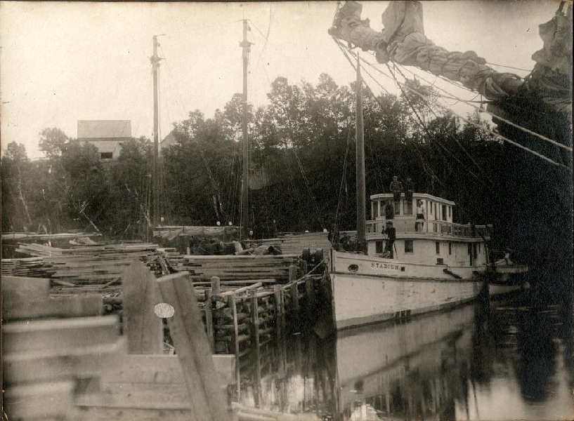 The Stadium, docked at unidentified wharf near Alma, was used as a tugboat to pilot ships in and out of the harbours near Alma. Note the lumber piles stacked on the dock waiting to be loaded on a ship and taken to market.