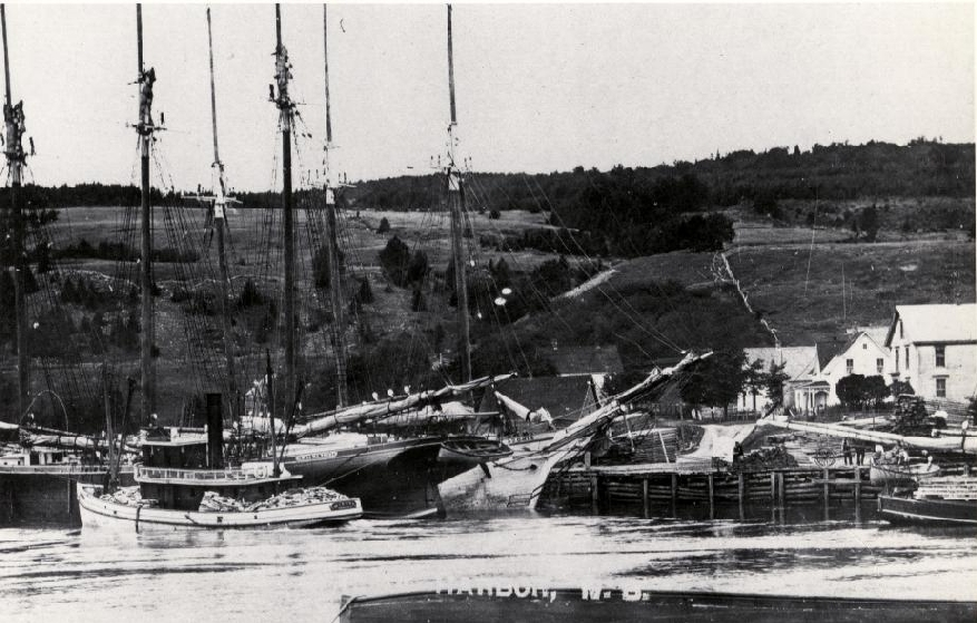 This photo of the harbour in Alma shows the tugboat Stadium beside two vessels tied to the dock. The dock in Alma was small so the vessels were tied together. They could be loaded with cargo when the tide, which is high in the picture, was in. When the tide was out the vessels would rest on the ocean floor.