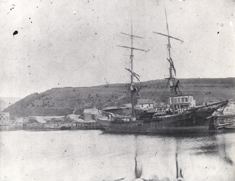 This vessel tied up at the harbour in Alma is probably being loaded with timber, the ship was used to transport the lumber to market. Note the wooden bridge across the Alma river in the far left of the photo, and the piles of logs ready to be sawed on the dock.