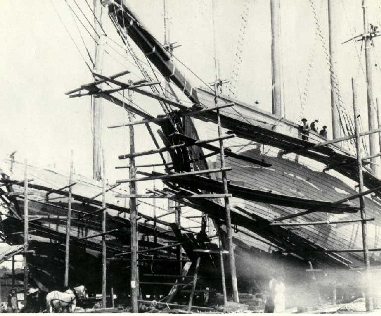 This photo shows two ships the Vincent and Meredith White being built side by side in Alma in 1915. Note the wooden scaffolding around the ships, workmen would build up this scaffolding higher and higher as the ship was being built.