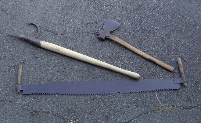 From right to left, an axe, a peeve, and a two man cross cut saw.