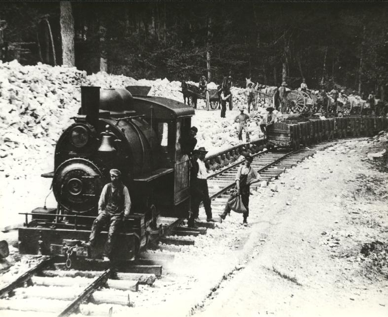 Gypsum being dumped from horse carts into ore cars.   1907