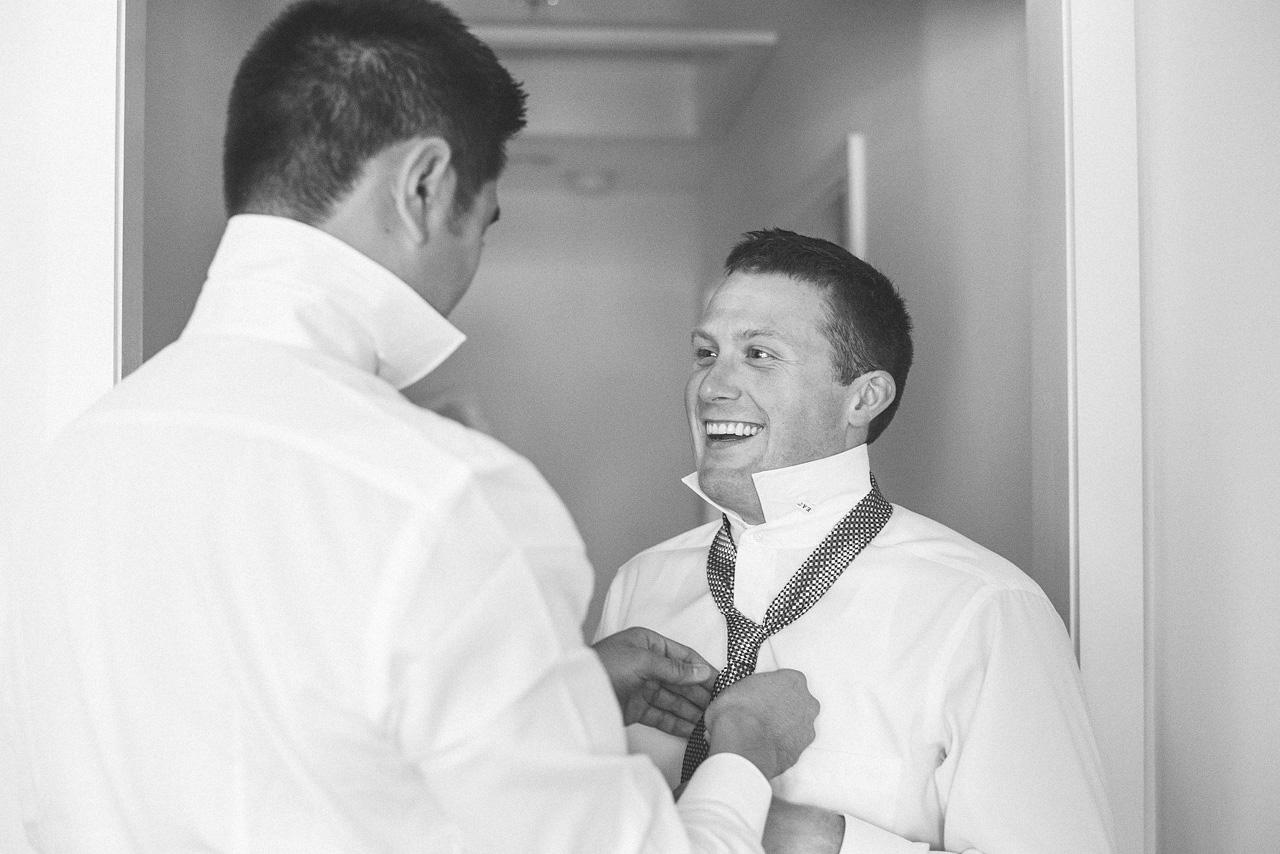 Groom getting help with tie