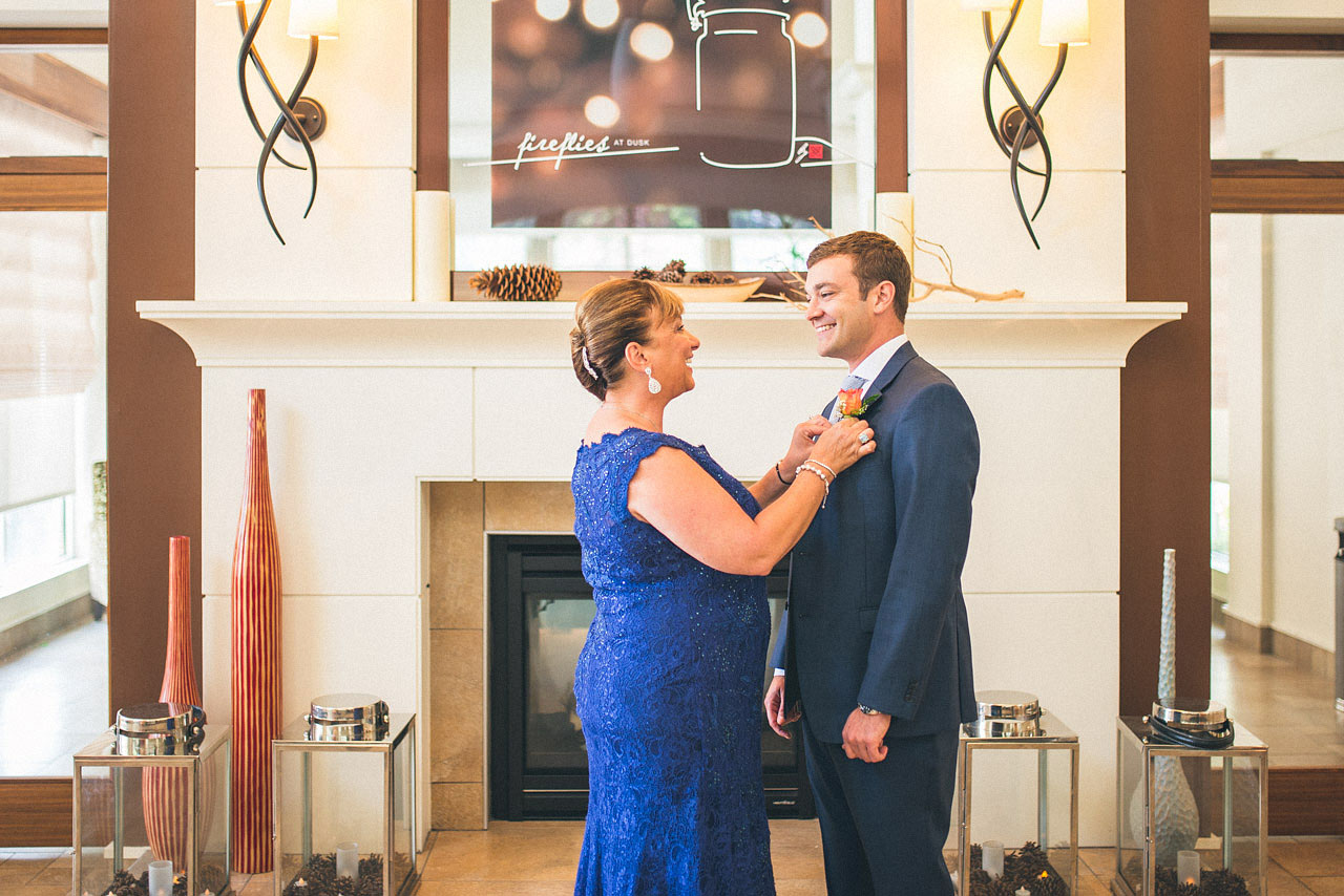 Mom helps Groom with boutonniere