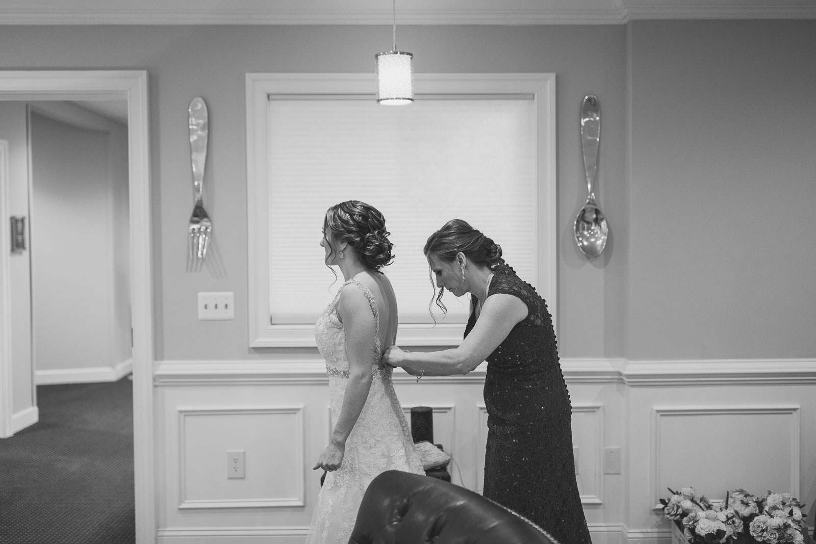 Mother helps bride put on dress