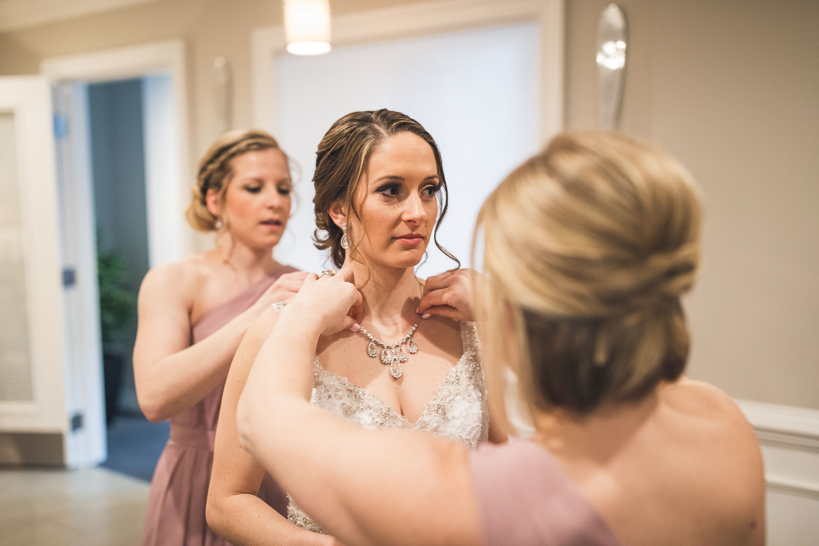 Bridesmaids Help Put on Necklace