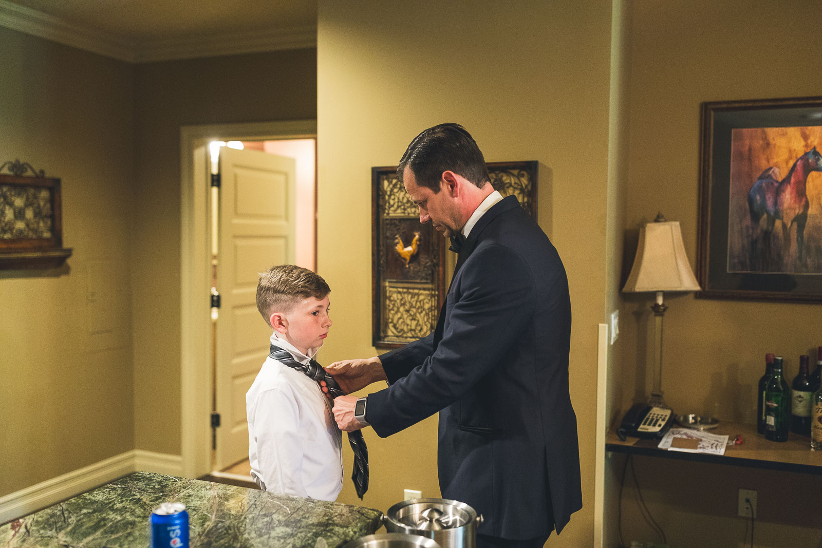 Groom helping young one with tie