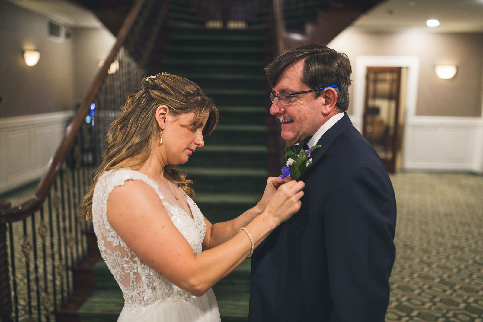 Bride puts boutineer on father