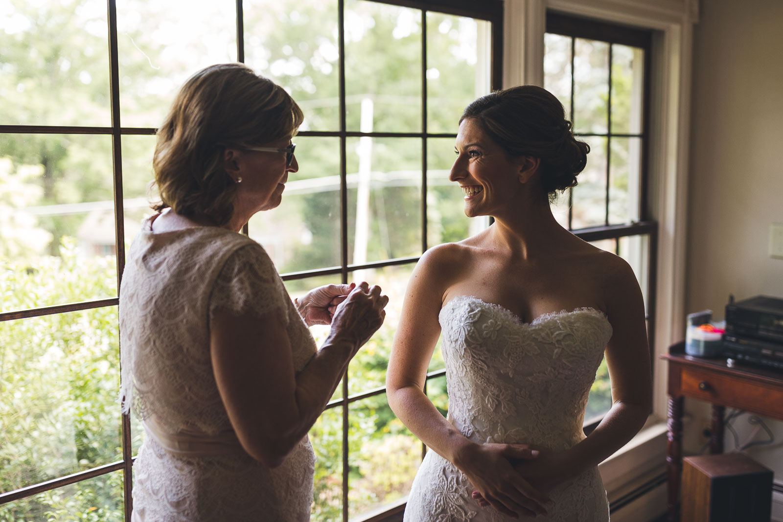 Mom puts ear rings on Bride