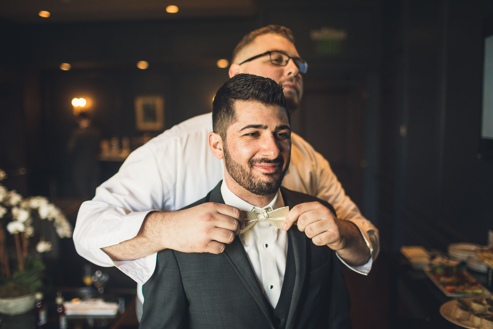 Best man helps adjust bowtie
