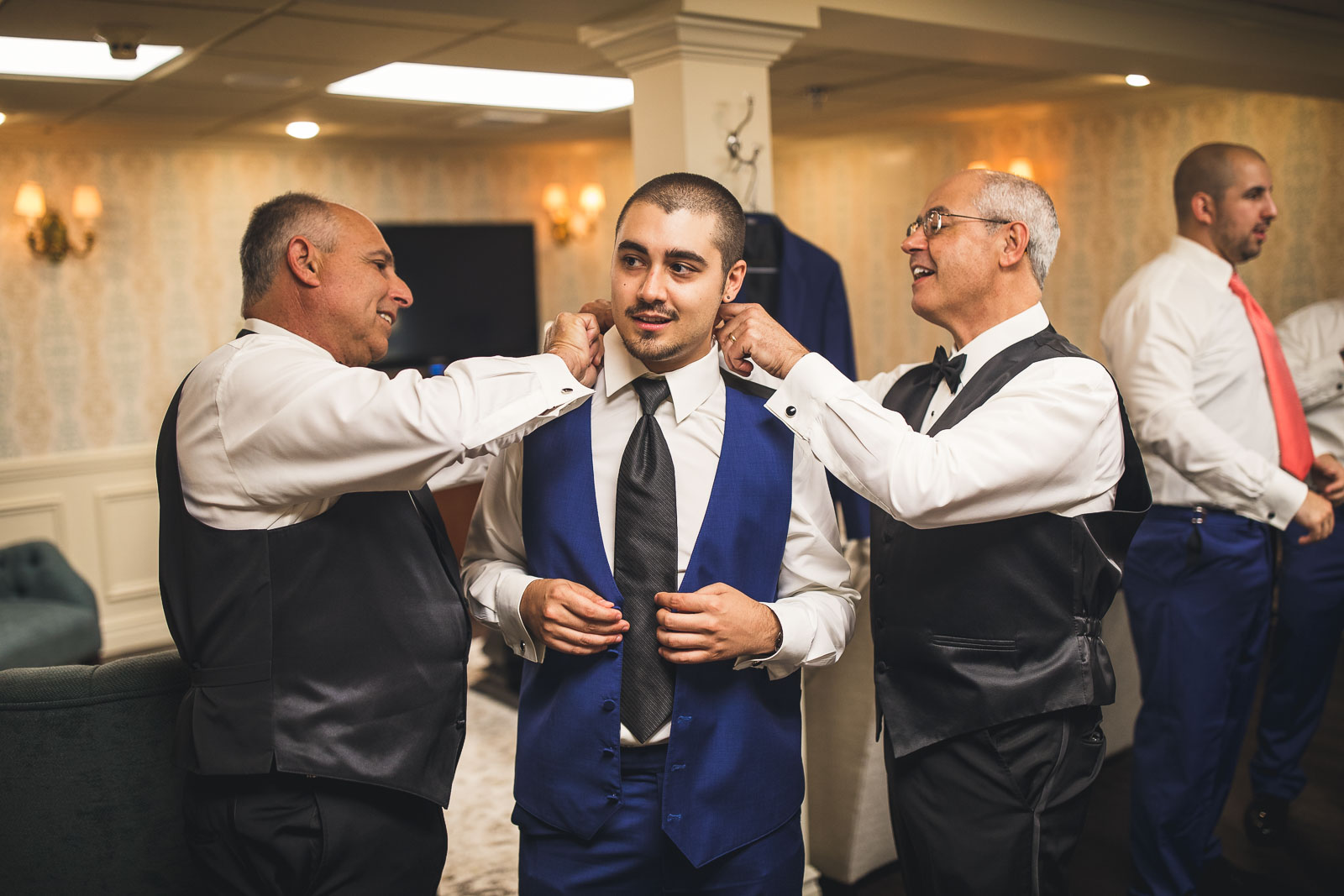 Fathers help Groom with Suit