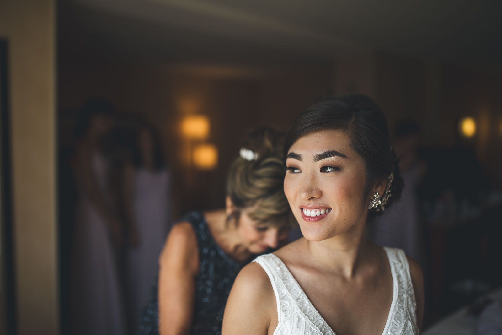 Bride gets dressed zipped up by Mom