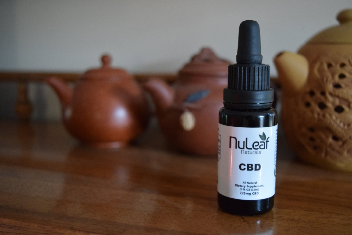NuLeaf Naturals CBD Oil Review - My Honest Thoughts and Experience With This Brand. Photo: Image of a bottle of CBD on a wooden counter, Amanda Linette Meder