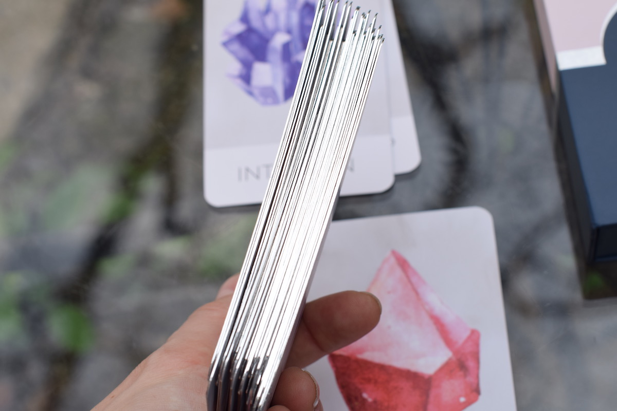 Article: Surely Serenity Oracle Deck // Intuitive Counsel // Thoughts + Inspiration Photo: Upclose of the card edges silver-gilded lining with Intuition and Foundation oracle cards in the background.