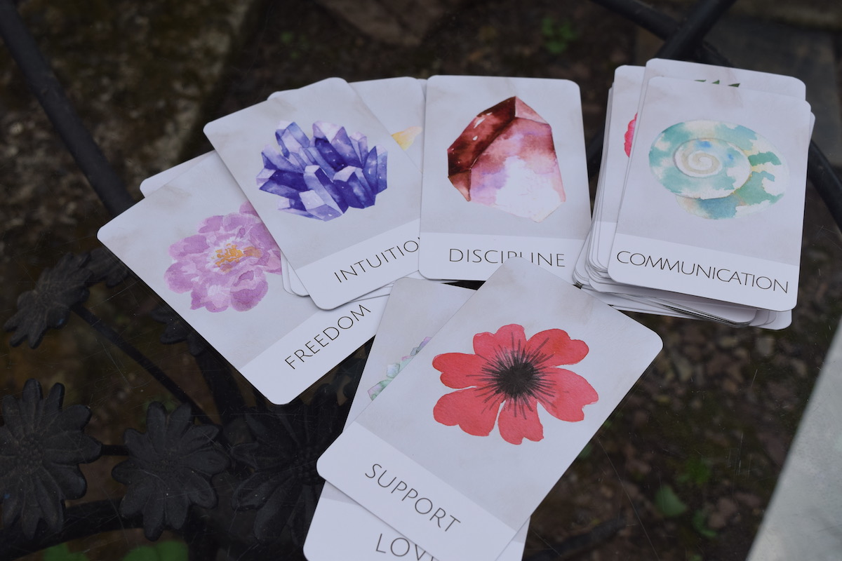 Article: Surely Serenity Oracle Deck // Intuitive Counsel // Thoughts + Inspiration Photo: Freedom, Intuition, Discipline, Communication, Support and Love Oracle Cards on a glass outdoor tabletop from the Surely Serenity Deck.