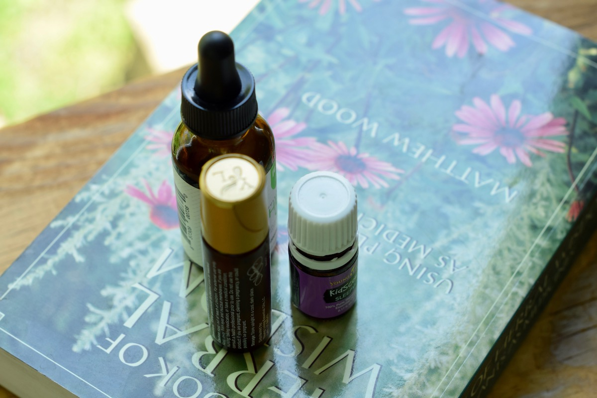 Natural Remedies To Help A Dog Pass Peacefully. Photo: Amanda Linette Meder, Image of three bottles of herbal supplements and tinctures on top of an herbal book.