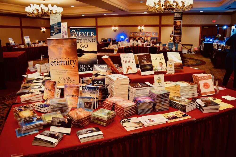 IANDS Conference 2019 Bookstore. Image of conference bookstore display of afterlife reading materials on table with red drape fabric Photo: Amanda Linette Meder