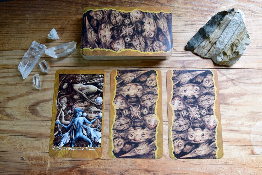Photo of The Faeries Oracle Card, Undressing of a Salad, with quartz crystal, desert jasper, and three backsides of cards on a wooden table by Amanda Linette Meder