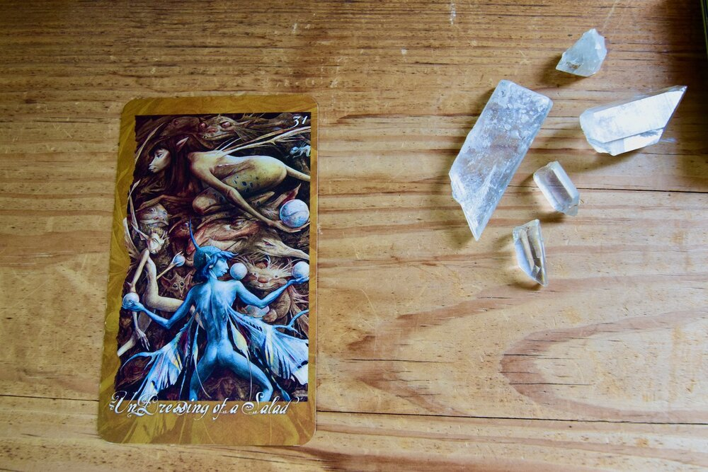 Photo of The Faeries Oracle Card, Undressing of a Salad with quartz crystal and selenite chips on a wooden table by Amanda Linette Meder