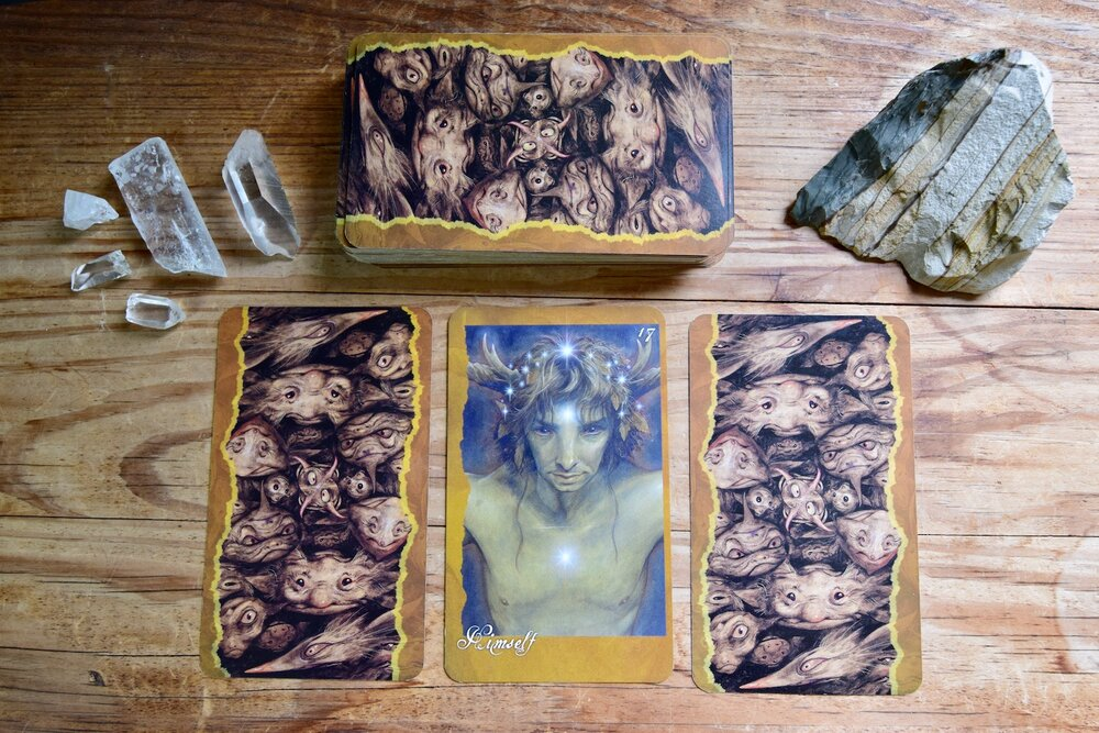Photo ofThe Faeries Oracle Card, Himself, and surrounded by three cards with backs up, quartz crystal and desert jasper on a wooden table by Amanda Linette Meder