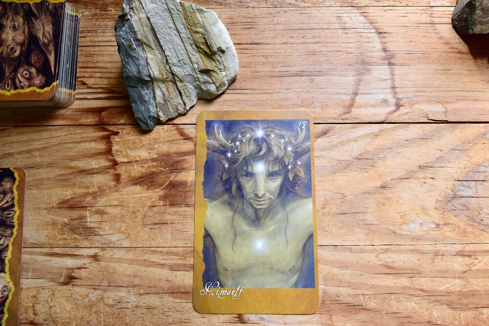 Photo ofThe Faeries Oracle Card, Himself, and a desert picture jasper on a wooden table by Amanda Linette Meder