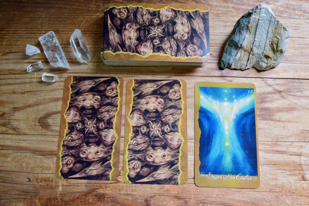 Photo of The Signers of the Chalice with quartz crystal, desert jasper, and three backsides of cards on a wooden table by Amanda Linette Meder