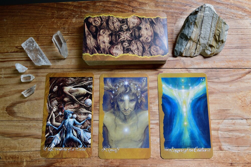 Photo of three of The Faeries Oracle Cards, Undressing of a Salad, Himself, and The Signers of the Chalice on a wooden table by Amanda Linette Meder