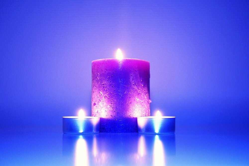 Photo of purple pillar candle with two blue tealight candles on blue background by StockSnap from Pixabay