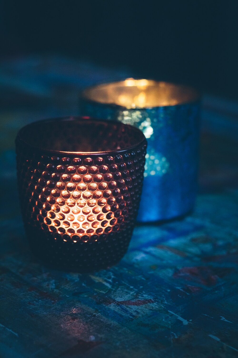 Photo of red candle in votive in front and blue votive in rear on textured surface by KatinkavomWolfenmond from Pixabay