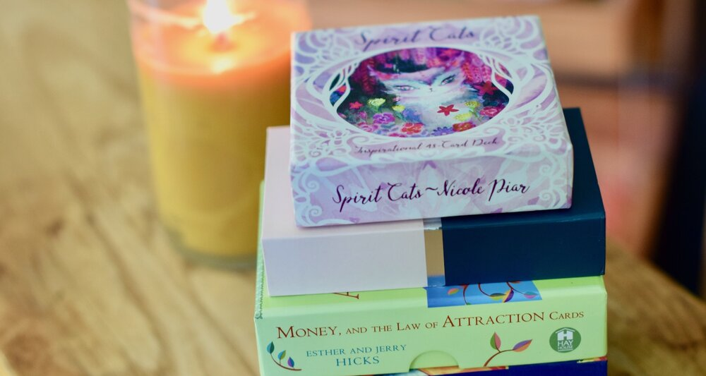 Photo of stack of Oracle Card Decks, from Spirit Cats to Money and the Law of Attraction Deck with candle in background by Amanda Linette Meder