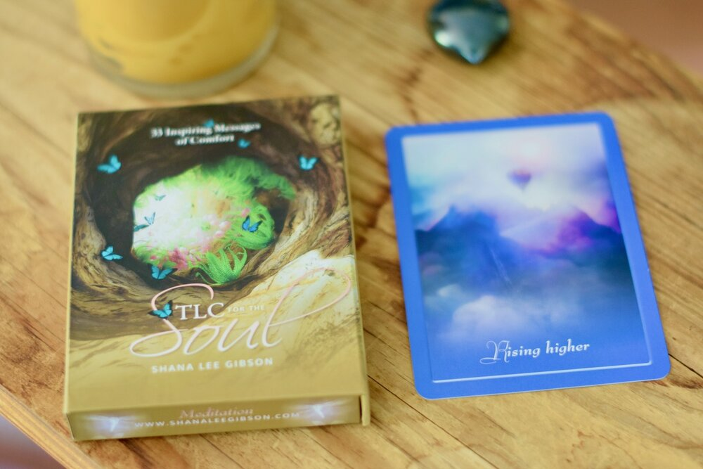 Photo of TLC for the Soul next to blue Rising Higher Card by Amanda Linette Meder
