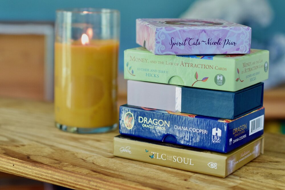 Photo stack of five positive Oracle Card Decks, from Spirit Cats to TLC for the Soul Deck with candle in background by Amanda Linette Meder