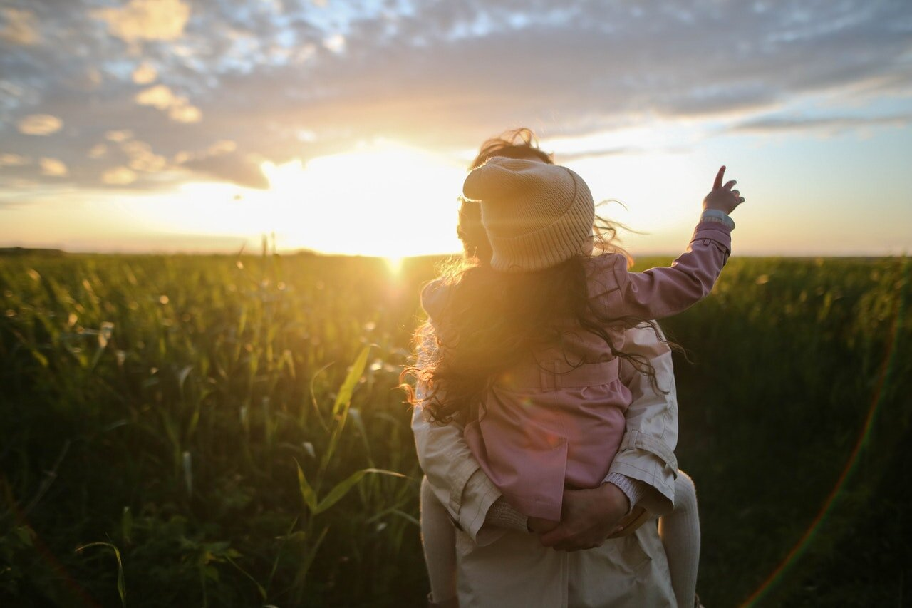 Photo of adult holding child in green field with golden light by Daria Obymaha 从 像素