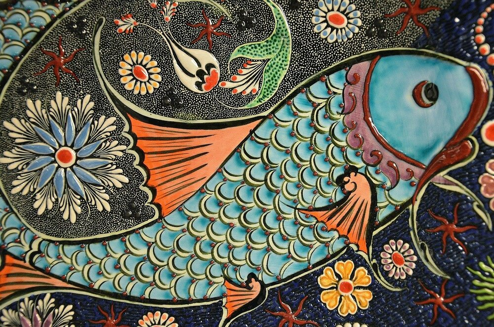 Photo of mosaic fish painted turquoise and coral by GLady from Pixabay