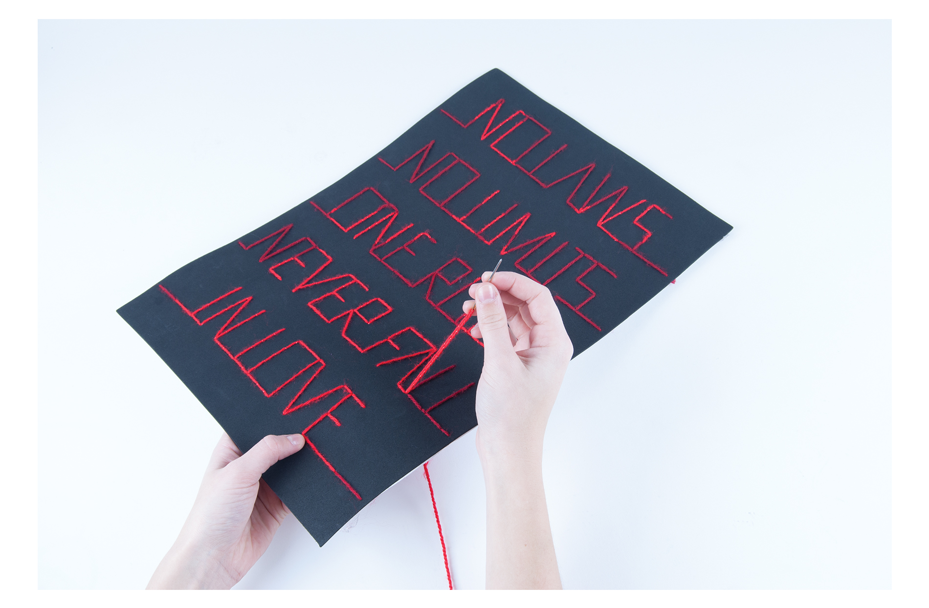 The famous tagline of the film Moulin Rouge is 'No laws, no limits, one rule: never fall in love was used as an inspiration for this handmade project. The type is all sown with the use of two different colours of wool. By using the brighter red, the shape of the mill is created inside the type.