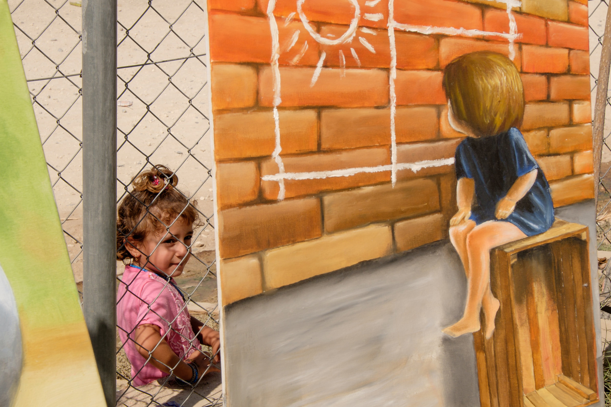 Kurdistan Region of Iraq. IDP Camp Kabarto II. A young girl watches the exhibition of Artist Saad Abduhamid Khalil from the outside. Khalil´s pictures were exhibited in the context of a chess tournament between to IDP-Camps, conducted by local NGO Harikar.