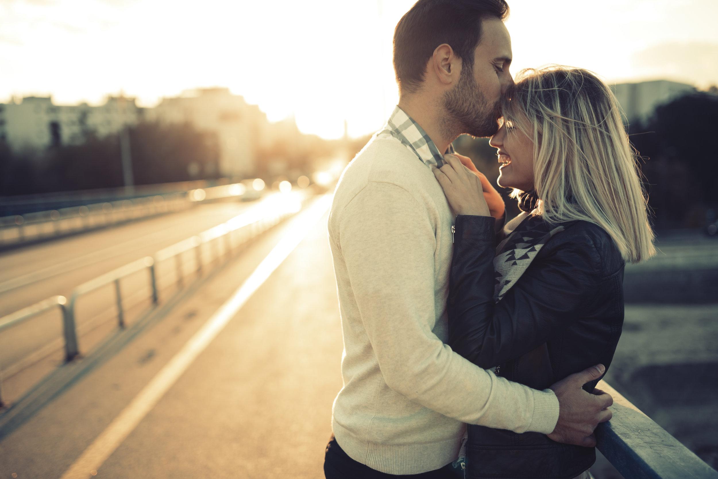 Couple kissing on a bridge smiling .jpg