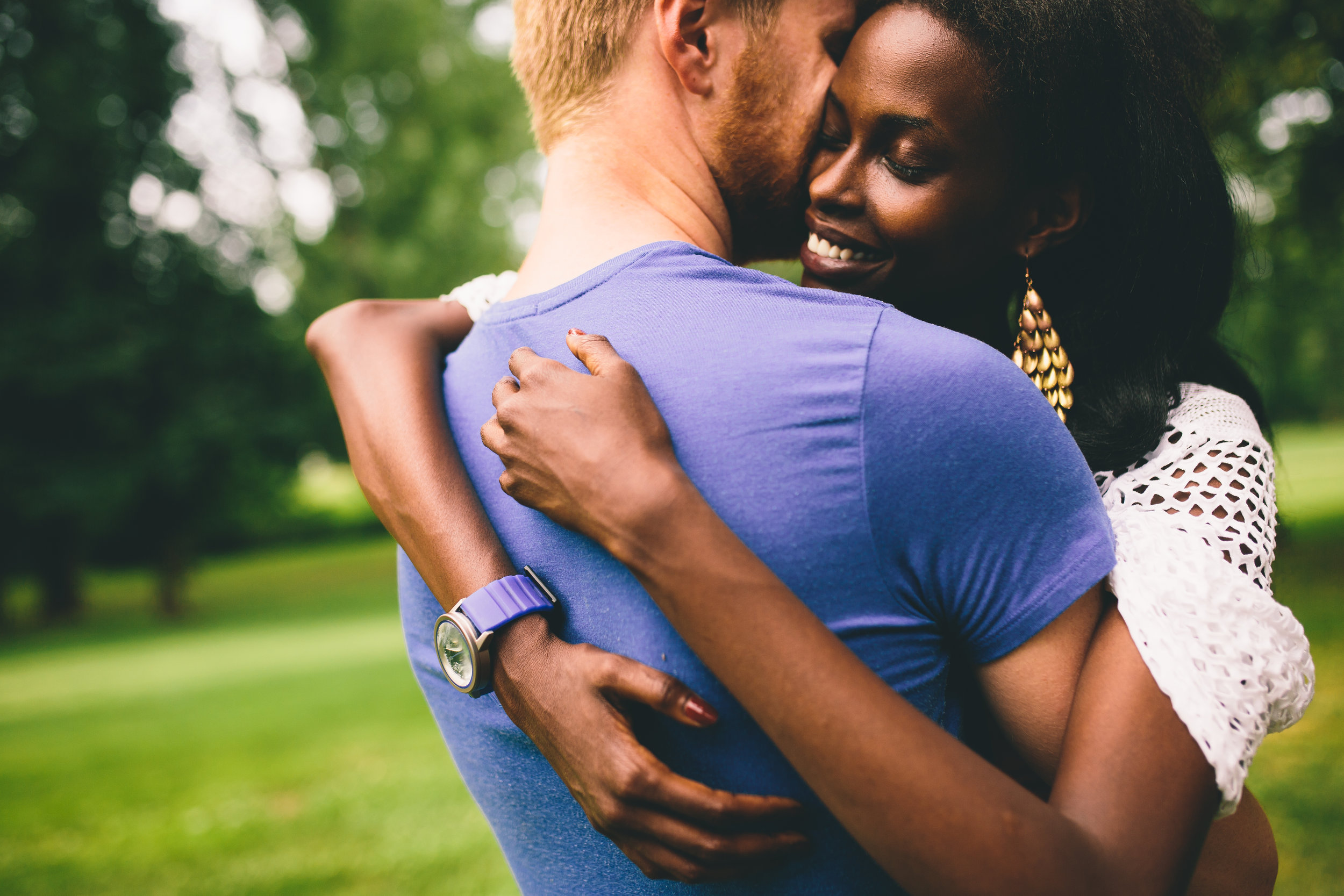 attractive interracial couple hugging in the park.jpg