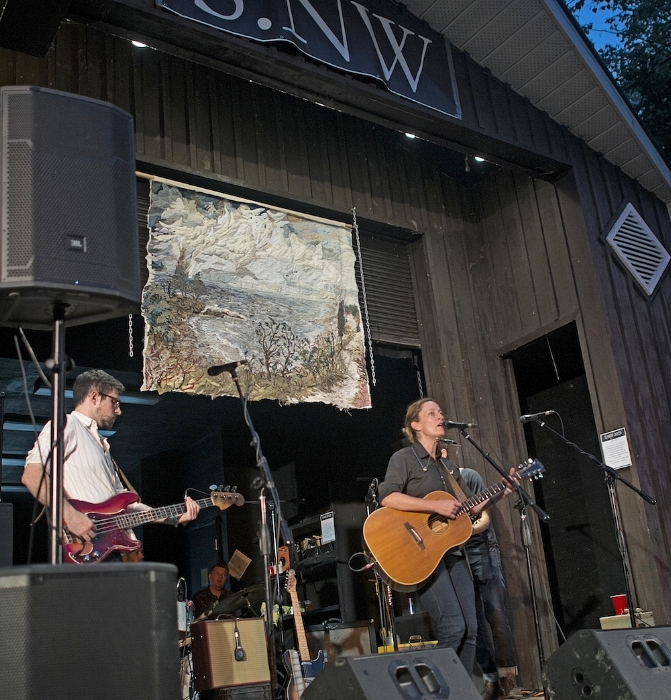 """Photo of musical talents with headliner, SARAH HARMER and up cycled textile art by Mihal Zada  Art on stage:  Secret Beach, Prince Edward County  at Sandbanks New Waves Festival in Sandbanks Provincial Park  Sarah Harmer played her newest song -  """"Just Get Here""""  from the  """"Al Purdy Was Here""""  documentary soundtrack  19 September 2015"""
