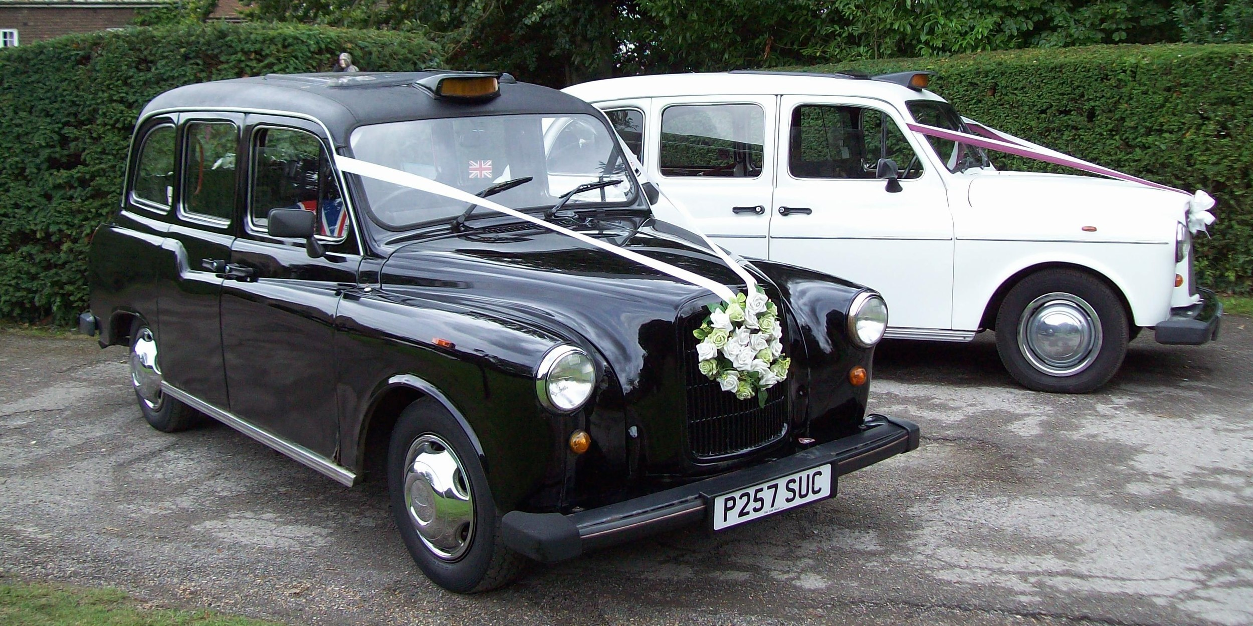 Pair of unusual wedding cars, the black and white London Fairway Taxi.