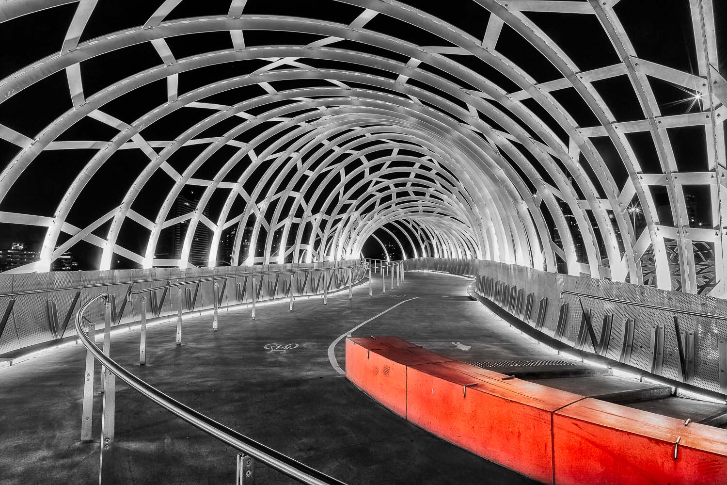 A red barrier provides a splash of    vibrant color    in this otherwise black and white photo of    Web Bridge    in the    Docklands    precinct of Melbourne, Australia.