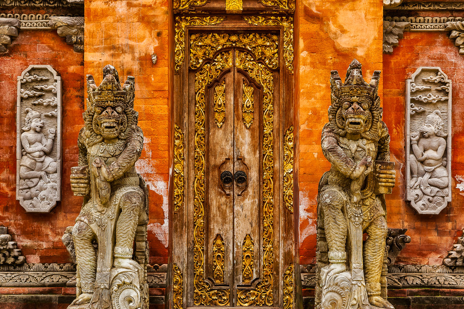 Ornately carved doorway    and    protective deities    mark the entrance to a    Hindu temple    in    Bali, Indonesia   .