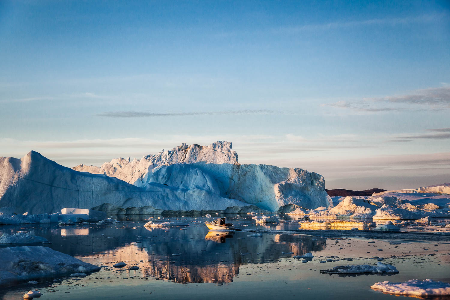 A small fishing boat amongst huge icebergs on the waters of the Ilulissat Icefjord near Ilulissat, Greenland.