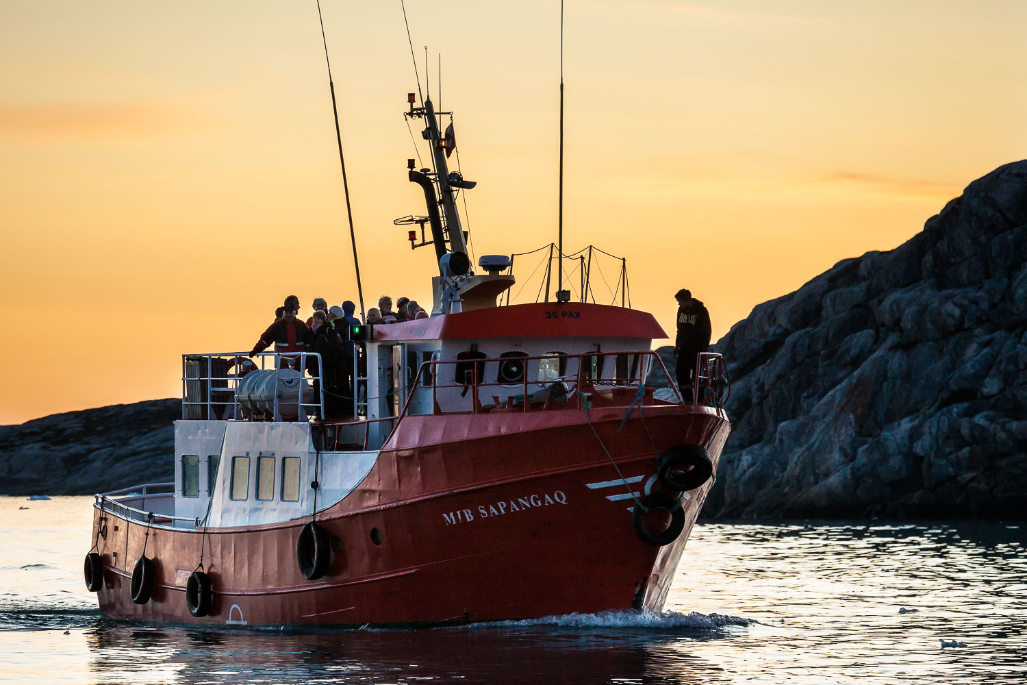 A ship brings passengers back to harbour at the end of a fabulous cruise exploring the Ilulissat Icefjord under the midnight sun near Ilulissat, Greenland.