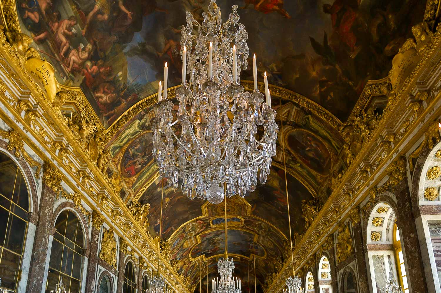 A magnificent chandelier against a famously ornate series of ceiling murals at the Palace of Versailles, France