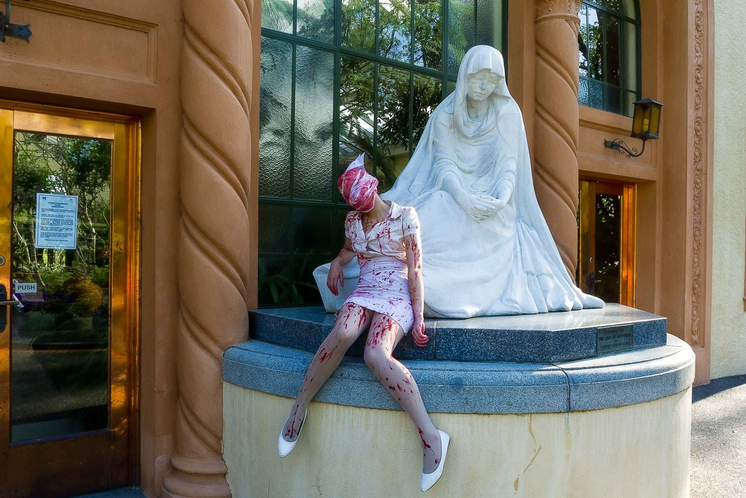 A  zombie nurse  resting outside the  Conservatory  in the  Fitzroy Gardens ,  Melbourne .