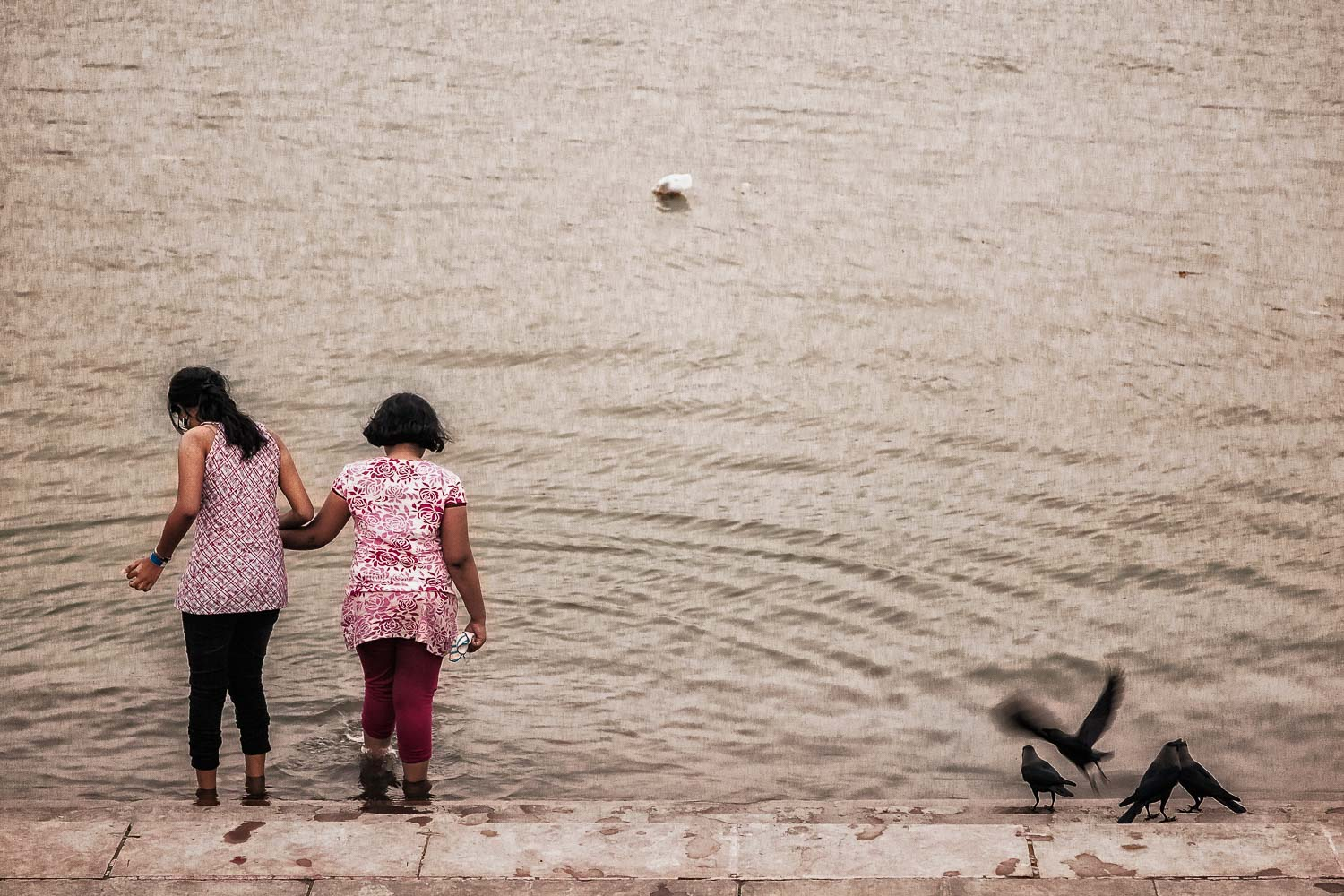 Two girls step gingerly into the waters of the    Hooghly River    in    Kolkata, India   . Version One.