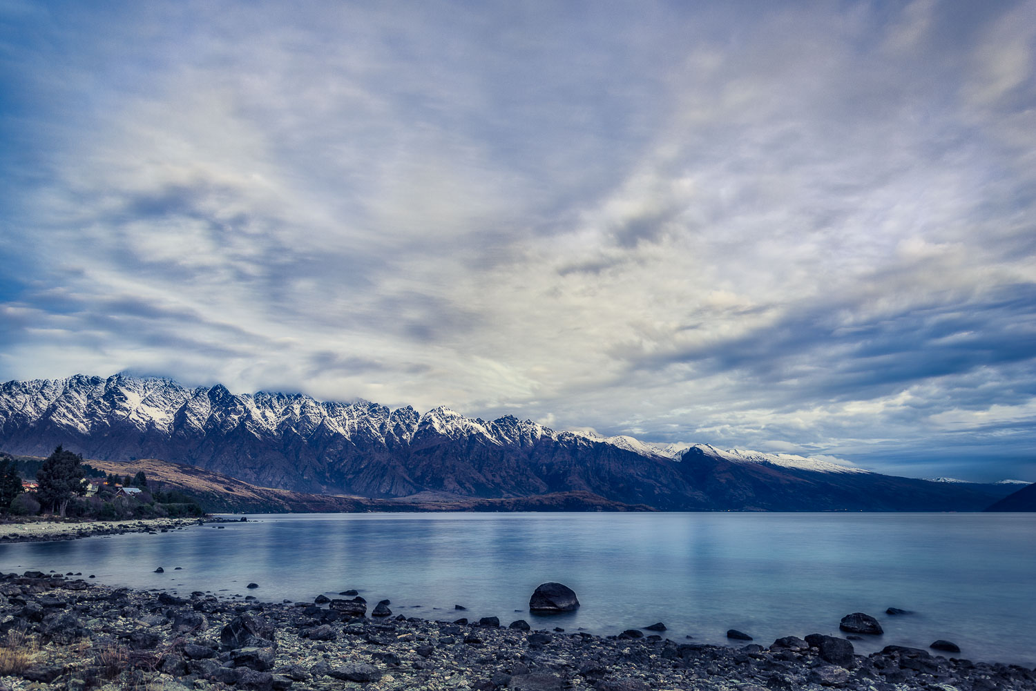 A dramatic sky over snow capped mountains above    Lake Wakatipu    near    Queenstown   ,    New Zealand   .