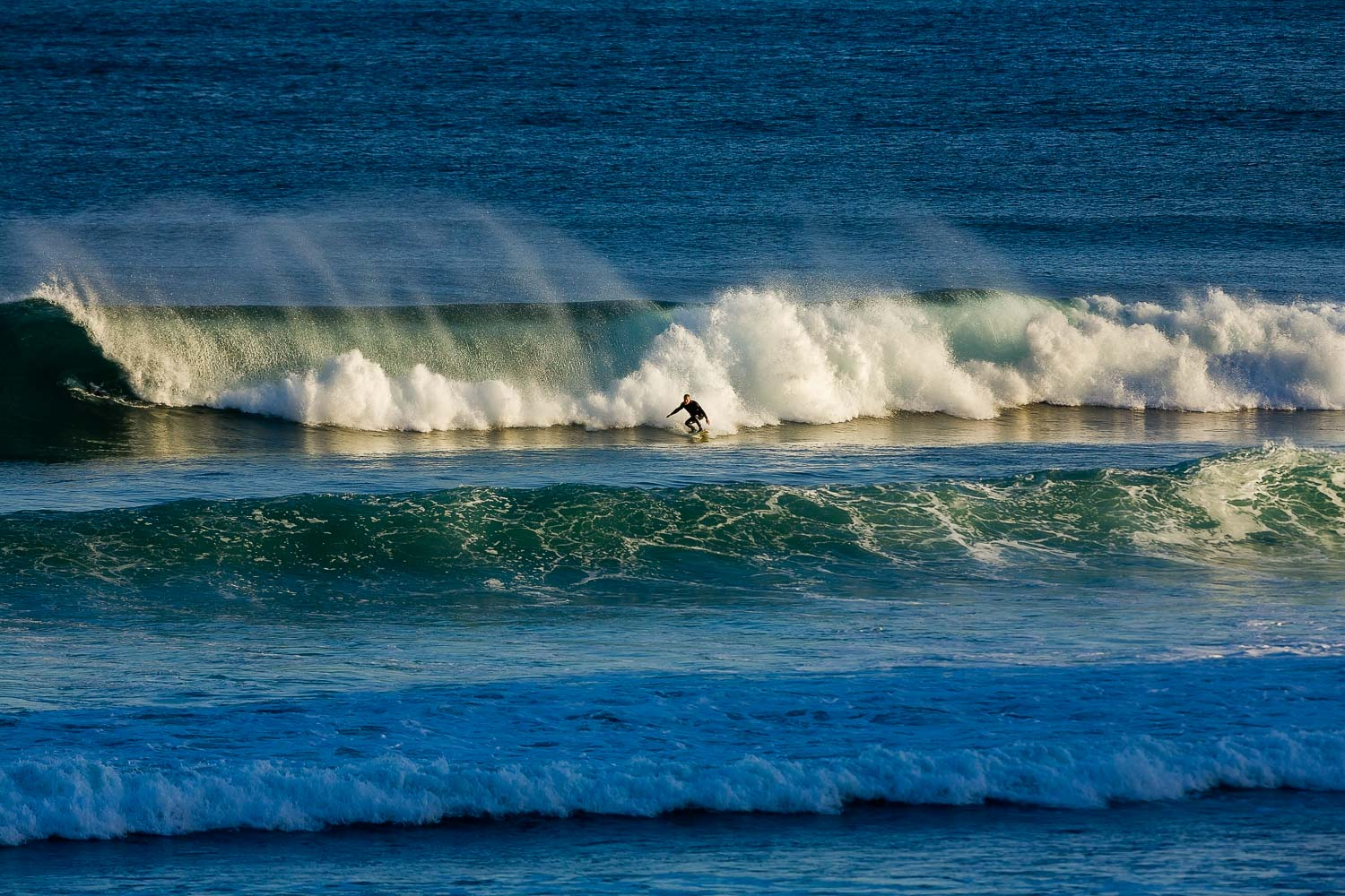 A surfer, catching the late afternoon rays at  Bells Beach , Australia.
